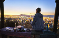 Chile, Santiago, woman drinking a beer in the mountains above the city at sunset - SSCF00090