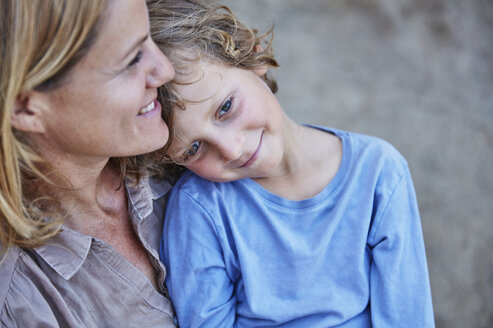 Smiling boy cuddling with mother outdoors - SSCF00105