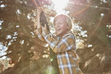 Happy boy swinging on a rope in backlight - SSCF00108