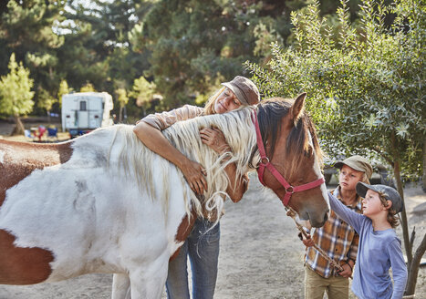 Woman with two sons cuddling with a horse - SSCF00111