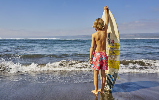 Chile, Pichilemu, boy standing at the sea with surfboard - SSCF00120