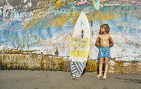 Chile, Pichilemu, boy standing at a colorful wall with surfboard - SSCF00123