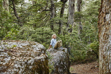 Chile, Puren, Nahuelbuta National Park, boy sitting on a rock in forest - SSCF00144