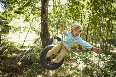 Boy balancing on tyres at an adventure park in forest - SSCF00156