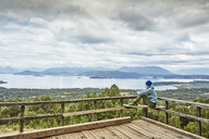 Chile, Puren, Nahuelbuta National Park, woman sitting on observation terrace overlooking the lake - SSCF00159