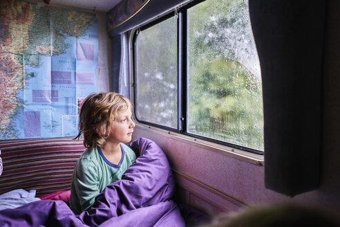 Boy in pyjama looking out of window of a camper - SSCF00162