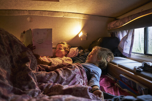 Mother looking at son's drawings lying in bed of a camper - SSCF00180