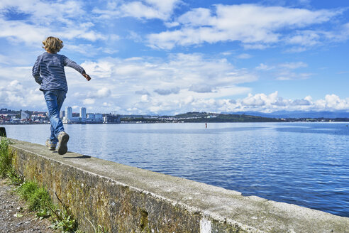 Chile, Puerto Montt, boy running on quay wall at the harbor - SSCF00183