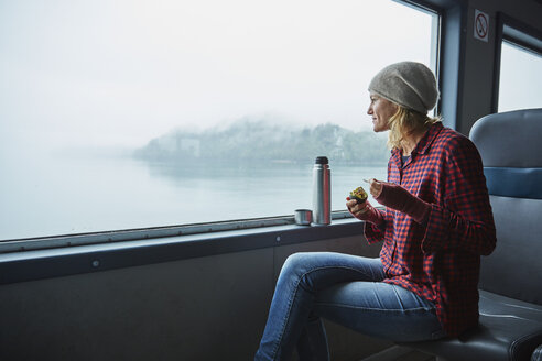 Chile, Hornopiren, woman looking out of window of a ferry eating an avocado - SSCF00189