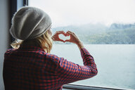 Chile, Hornopiren, woman shaping a heart with her hands at the window of a ferry - SSCF00201