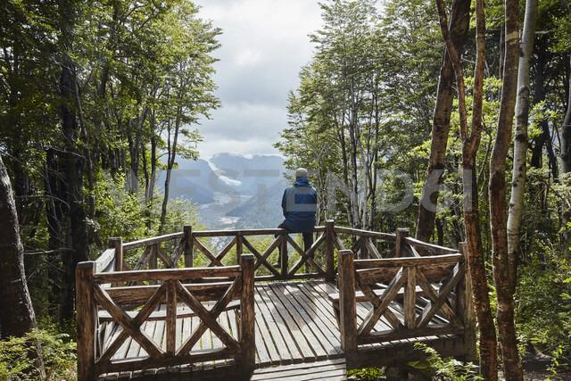 Chile, Chaiten, Parque Pumalin, man sitting on observation deck looking at glacier - SSCF00210 - Stefan Schütz/Westend61