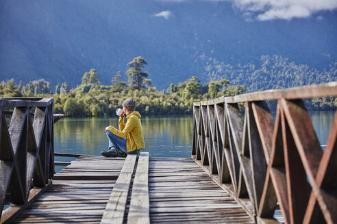 Chile, Chaiten, Lago Rosselot, woman sitting on jetty drinking from mug - SSCF00216