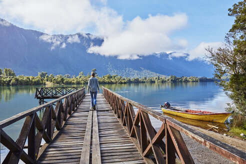 Chile, Chaiten, Lago Rosselot, woman walking on jetty - SSCF00219