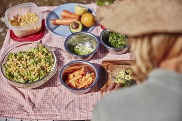 Woman preparing vegetarian food at outdoor table - SSCF00222