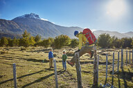 Chile, Cerro Castillo, mother with two sons on a hiking trip jumping over paddock fence - SSCF00228