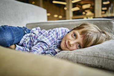 Portrait of boy lying on couch with earphones - SSCF00255