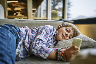 Boy lying on couch with earphones and mp3 player - SSCF00258