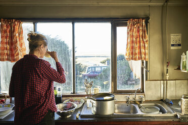 Woman standing in kitchen preparing meal and drinking from cup - SSCF00264