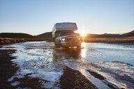 Chile, Tierrra del Fuego, Lago Blanco, camper crossing river at sunset in the steppe - SSCF00270