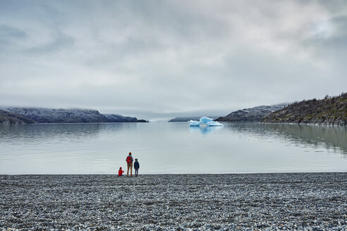 Chile, Torres del Paine National park, Lago Grey, woman with two sons standing at the shore looking at iceberg - SSCF00276