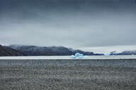 Chile, Torres del Paine National park, Lago Grey, stony shore and iceberg in water - SSCF00279
