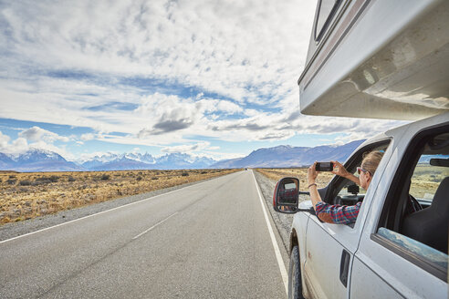 Argentina, Patagonia, El Chalten, woman taking cell phone picture in camper on road towards Fitz Roy - SSCF00300