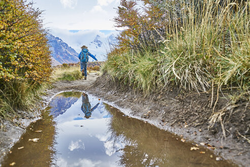 Argentina, Patagonia, El Chalten, boy running at puddle at Cerro Torre in Los Glaciares National park - SSCF00306