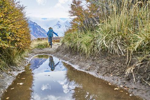 Argentina, Patagonia, El Chalten, boy running at puddle at Cerro Torre in Los Glaciares National park - SSCF00306