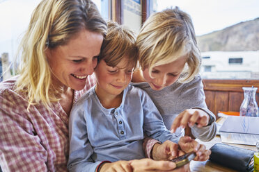 Happy mother with two sons sitting at table in a cafe playing with cell phone - SSCF00318