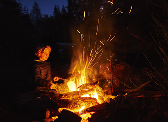 Argentina, Patagonia, Lago Futalaufquen, boy at camp fire at night - SSCF00333