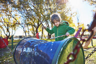 Boy drumming on cask on playground - SSCF00336