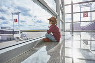 Boy sitting behind windowpane at the airport looking at airfield - SSCF00342