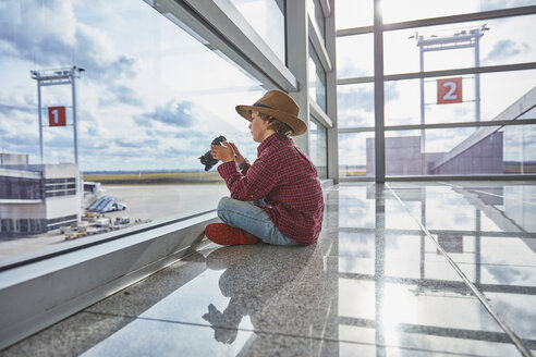 Boy sitting behind windowpane at the airport holding a camera - SSCF00345