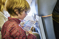Boy sitting on an airplane reading safety instructions - SSCF00348