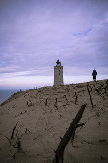 Denmark, North Jutland, back view of man looking at Rubjerg Knude Lighthouse at blue hour - REAF00482