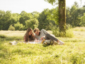 Young couple relaxing with baby girl on blanket in nature - LAF02187
