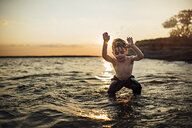 Carefree shirtless boy playing in river against sky during sunset - CAVF59215
