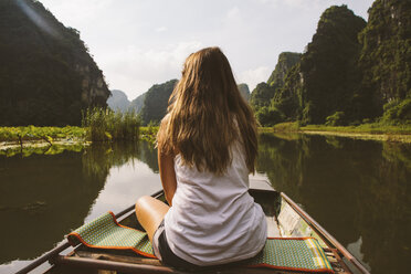 Rear view of woman looking at view while traveling in boat on river - CAVF59230
