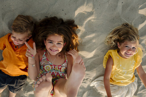 High angle portrait of happy sisters lying with brother at beach - CAVF59308