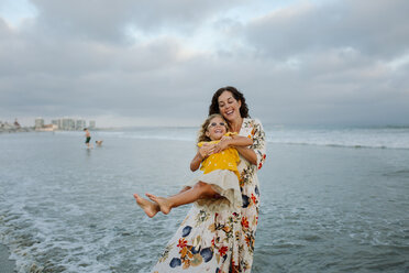 Playful mother spinning daughter at beach against cloudy sky - CAVF59311
