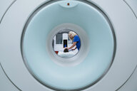 Nurse preparing patient for MRI Scan in hospital seen through scanner - CAVF59374
