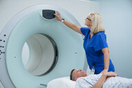 Nurse adjusting button on MRI Scanner while patient lying in examination room - CAVF59377