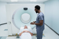 Side view of male nurse talking with patient lying for MRI Scan in examination room - CAVF59380