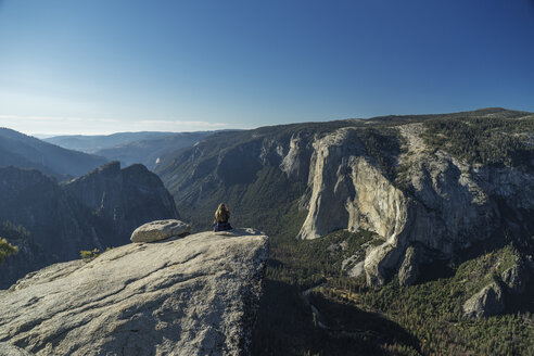 Woman sitting on cliff at Yosemite National Park against blue sky - CAVF59383