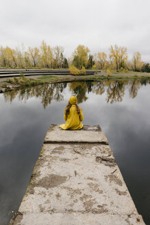 High angle view of thoughtful woman sitting on pier over lake - CAVF59392