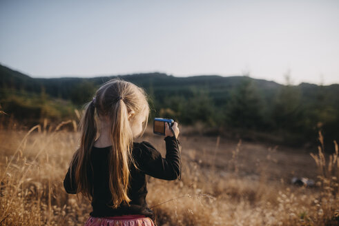 Girl with pigtails photographing while standing on field - CAVF59401