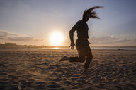 Silhouette man dancing at beach against sky during sunset - CAVF59434