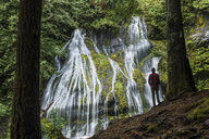Rear view of man standing against waterfall at Gifford Pinchot National Forest - CAVF59461