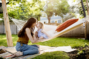 Daughter kissing mother while sitting in hammock at yard - CAVF59476