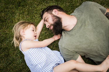 High angle view of father with daughter lying on grassy field at yard - CAVF59482